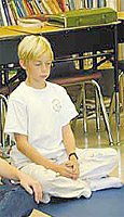 Young boy seated in meditation posture