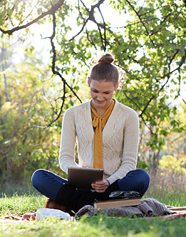 lady sitting on a blanket outside reading a tablet