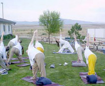 Nikki leading yoga postures class outside, with inmates