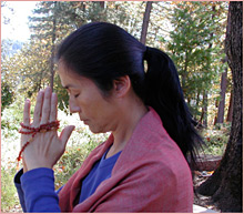 Prayer with mala beads in the forest